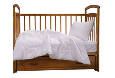Wooden cot with bedding Stock Photos