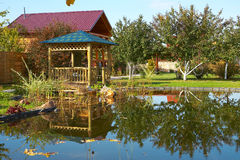 Wooden cottage. House and pond stock photography
