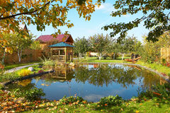 Wooden cottage. House and pond stock images