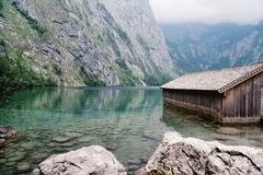 Wooden cottage in beautiful lake in the Alps with misty mood.  Royalty Free Stock Images