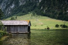 Wooden cottage in beautiful lake in the Alps with misty mood.  Stock Images