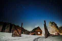 Wooden cottage with blue starry sky at night royalty free stock photos