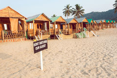 Wooden cottage and cabins of sandy beach resort with sign Dont Disturb Our Guests.  Royalty Free Stock Photos