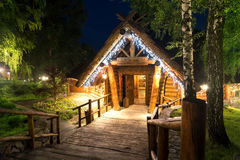 Wooden cottage in forest lit by lanterns Royalty Free Stock Photo