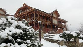 Wooden cottage in mountain village during heavy snowfall with coniferous forest on background. Snow falling on log. Chalets with stone chimney and wall at ski stock footage
