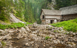 Wooden cottage in the mountains with creek Royalty Free Stock Images
