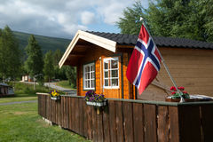 Wooden cottage with Norwegian flag, Norway. Wooden cottage on a campsite with Norwegian flag, Norway Royalty Free Stock Photos