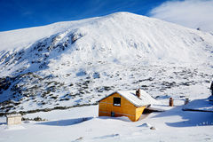 Wooden cottage on the peak of a Snow Mountain Stock Photography