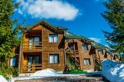 Wooden cottage among pine forest. Comfortable accommodation in the ski resort Bukovel. Polianitsa village, Ivanofrankivsk region, Ukraine - February 26, 2019 royalty free stock image