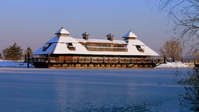 Wooden cottage on the river in winter evening. Royalty Free Stock Images