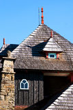Wooden cottage with a shingle roof. And a stone pillar in Moravia, Czech Republic Stock Image