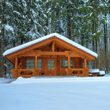 Wooden cottage in snowy forest Royalty Free Stock Photo