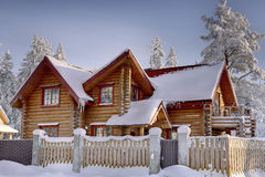 Wooden cottage of stained timber, snowy woods in winter. Stock Photos