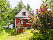 Wooden cottage and well on backyard in village Stock Photography