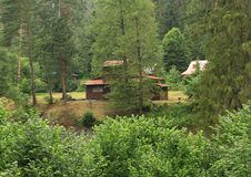 Cottages in Slovak Paradise. Wooden cottages behind bushes, trees and river Hornad on meadow in forest in Slovak national park Slovak Paradise in Slovak Republic royalty free stock image