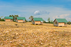 Wooden cottages. In the field Stock Photography