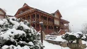 Wooden cottages in mountain village during heavy snowfall with coniferous forest on background. Snow falling on log. Chalets with stone chimney and wall at ski stock footage
