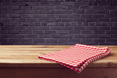 Wooden counter background with red checked tablecloth over black brick wall Royalty Free Stock Photos