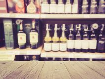 Wooden counter product display with Wine Liquor bottle. On shelf, Blurred background Royalty Free Stock Photo