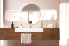 Wooden counter and round mirror on the wall. A set of wooden counter and round mirror are attached with the wall in luxury bathroom royalty free stock photos