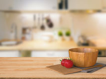 Wooden counter top with tomato and wooden bowl Royalty Free Stock Photo