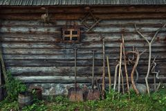 Wooden barn wall  texture and farming tools. Wall of an ancient wooden country barn and farming tools, Lithuania. Exterior detail Stock Photography