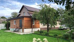 Wooden country house with sunny backyard. Apple trees are full of ripe apples, car parking on pathway
