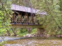 WOODEN COVERED BRIDGE OVER THE RIVER Stock Image
