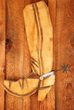 Wooden Cowboy Boot with Spur on Wooden Wall Stock Photo
