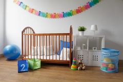 Wooden cradle in cosy bedroom stock image