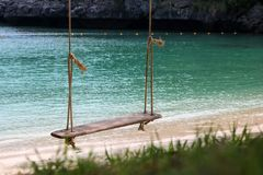 Wooden cradle hanging on the beach with ocean views. Wooden cradle or swing hanging on the beach with nature and ocean views background Royalty Free Stock Photo