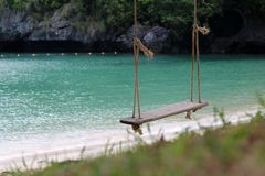 Wooden cradle or swing hanging on the beach. With nature and ocean views background Royalty Free Stock Photo