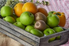 Oranges,kiwis and apples in a wooden crate. A wooden crate containing oranges, kiwi and apples stock photos