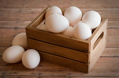 Wooden Crate of Fresh Eggs on a wood plank background board. A dozen fresh eggs inside a wooden crate container with a wooden plank board for the background royalty free stock image
