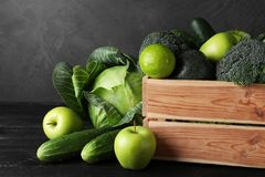 Wooden crate, fresh green fruits and vegetables. On dark background royalty free stock image