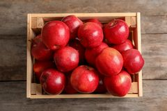 Wooden crate with fresh red apples on table. Top view stock images