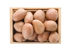 Wooden crate with fresh ripe organic potatoes on white background. Top view stock photos