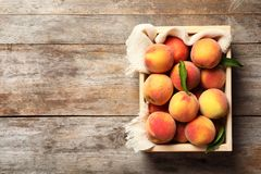 Wooden crate with fresh sweet peaches. On table, top view stock images