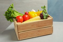 Wooden crate with fresh vegetables. On gray table stock images