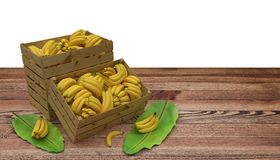 Wooden crates or boxes full of bananas place on wooden table. And banana leaf next to. Isolated on White. stock image