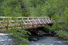 Wooden Creek Bridge In Forest. A large wooden bridge spanning a creek in the forest stock photography