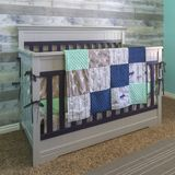 Wooden crib draped with quilt stock image