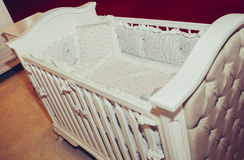 Wooden crib and retro silk bedding and pillows. In modern home Royalty Free Stock Photos