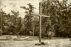 Wooden cross  against a dramatic forest. Vintage style Royalty Free Stock Photography