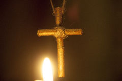 A wooden cross against the flames of the candle Royalty Free Stock Images