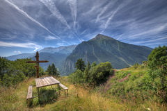 Wooden cross on alpine meadow. Royalty Free Stock Image