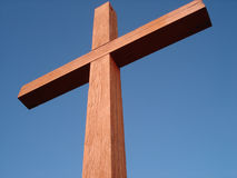 Wooden Cross at Angle. View looking up at a wooden cross in sunlight against a blue sky Royalty Free Stock Photos