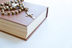 The wooden cross and black bible on wooden background. The wooden cross and black bible with flowers on wooden background Royalty Free Stock Image