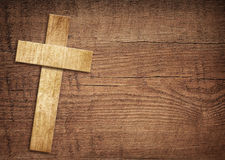 Wooden cross on brown old tabletop or wall surface Stock Photography