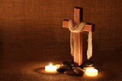 Wooden cross by candlelight and stones with shabby background Royalty Free Stock Photography